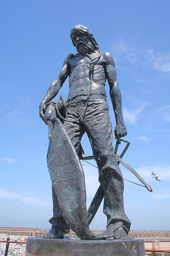 The Mariner with albatross about his neck and crossbow in his hand.